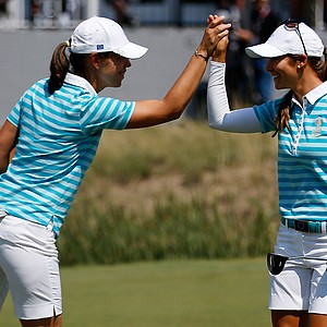 Karine Icher of France and the European team celebrate with Azahara Munoz of Spain after making a putt on the 16th green during the monring Foursome matches for the 2013 Solheim Cup.