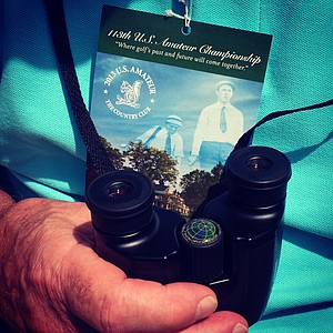 A spectator armed with binoculars during the semifinals at the 2013 U. S. Amateur at The Country Club.