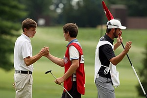 Matt Fitzpatrick shakes hands with his brother/caddie Alex after the conclusion of the first 18 holes of the finals at the 2013 U. S. Amateur at The Country Club. Fitzpatrick was 1 up after 18.