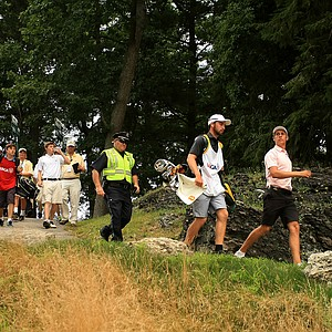 Oliver Goss walks down the path from the 15th tee during the finals at the 2013 U. S. Amateur at The Country Club.