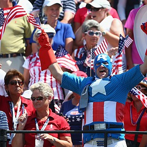 A fan cheers on the U.S. in on the first tee during the final day singles matches of the 2013 Solhiem Cup.