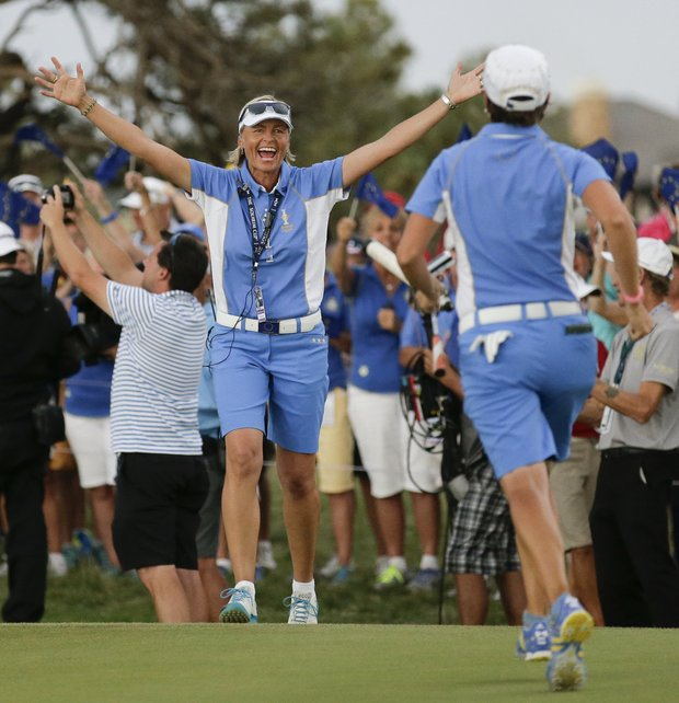 European captain Liselotte Neumann reaches out to Catriona Matthew after the team clinched victory at the 2013 Solheim Cup at Colorado Golf Club.
