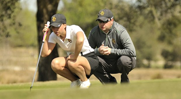 Baylor coach Jay Goble helps Emma Carberry read a putt.