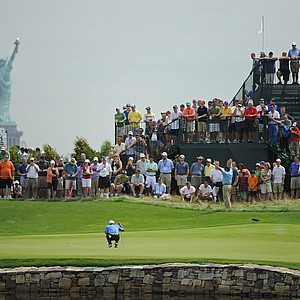 Tiger Woods lines up a putt in the shadow of the Statue of Liberty during the first round of the 2013 Barclays at Liberty National.