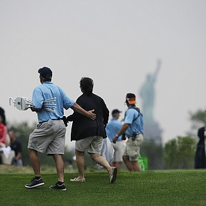 A gallery looks on under the shadow of the Statue of Liberty during the first round of the 2013 Barclays at Liberty National.
