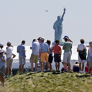 The gallery at The Barclays stands with the Statue of Liberty in the background during Saturday play at Liberty National to watch the first event of the PGA Tour's 2013 FedEx Cup.