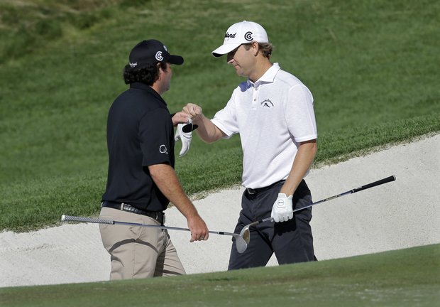 George McNeill (right), after holing out from the 18th bunker, is congratulated by Steven Bowditch during Saturday play at Liberty National in The Barclays, the first event of the PGA Tour's 2013 FedEx Cup.