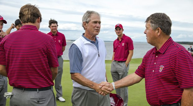 U.S. captain Jim Holtgrieve (right) greets former president George W. Bush on Thursday at National Golf Links.