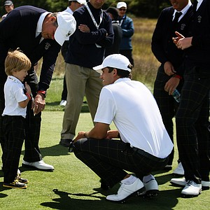 Cory Whitsett chats with Captain Jim Holtgrieve's grandson, Walker Kast, during Friday's practice at the 2013 Walker Cup at National Golf Links of America in Southampton, N.Y.