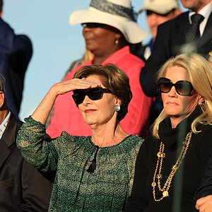 Laura Bush watches her husband former President George W. Bush as he speaks at the opening ceremony of the 2013 Walker Cup at National Golf Links of America in Southampton, N.Y.