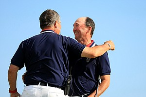 USA captain Jim Holtgrieve gives Todd White a hug after he won his match during Sunday singlesof the 2013 Walker Cup at National Golf Links of America in Southampton, N.Y.