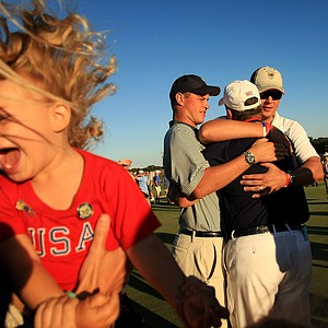 Ava Holtgrieve, 2, granddaughter of USA captain Jim Holtgrieve celebrates while her grandpa gets hugs during Sunday foursomes of the 2013 Walker Cup at National Golf Links of America in Southampton, N.Y.