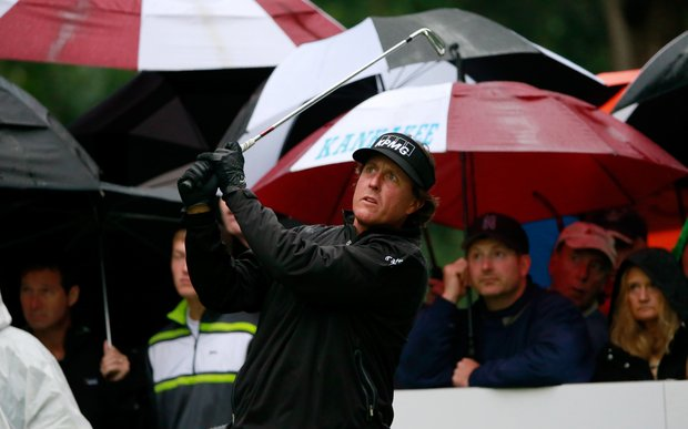 The gallery takes cover while watching Phil Mickelson during Sunday's rainy final round of the 2013 BMW Championship, the third event of the PGA Tour's FedEx Cup playoffs, at Conway Farms near Chicago.