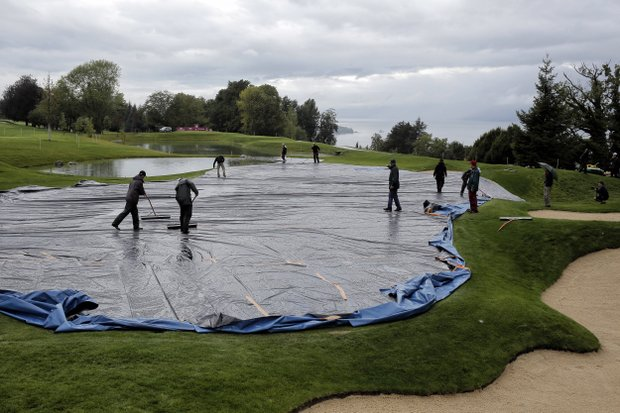 Crews at Evian Masters GC work to move water away from the fifth green and remove the tarp that protected it and other greens at the course from overnight rains.