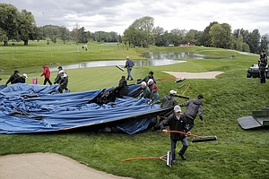 Crews at Evian Masters GC work to move water away from the fifth green and remove the tarp that protected it and other greens at the course from overnight rains before the final round of the 2013 Evian Championship.
