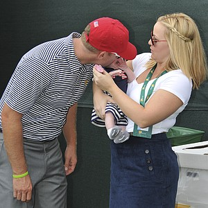 Hunter Mahan kisses his daughter while wife Kandi Mahan looks on during Day 2 of the Presidents Cup.