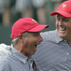 United States' Phil Mickelson (right) and team captain Fred Couples laugh together while walking down the first tee during a foursome match against the International team at the Presidents Cup.