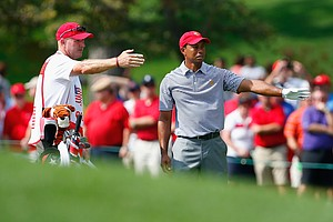 Tiger Woods of the U.S. and his caddie Joe LaCava line up a shot on the first hole during the Day 2 foursome matches at Muirfield Village.