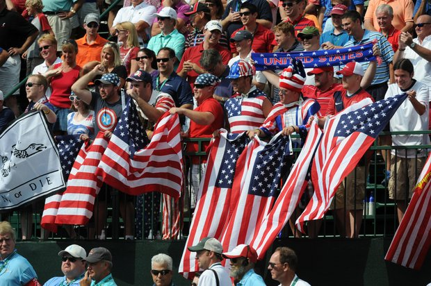 Fans waves flags on the first hole during the Day 2 foursomes matches at the Presidents Cup.