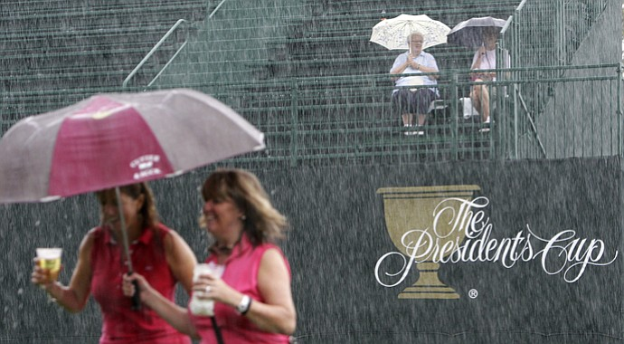 Fans brave the rain during a weather delay Friday at the Presidents Cup at Muirfield Village Golf Club.