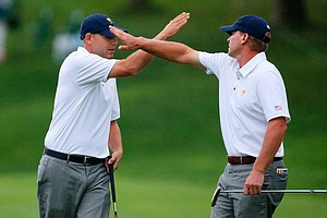 Steve Stricker (left) and Bill Haas of the U.S. celebrate winning the 14th hole during the weather-delayed Day 3 foursome matches.