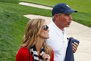 U.S. Team Captain Fred Couples walks off the 18th green with his girlfriend Nadine Moze after the U.S. Team defeated the International Team 18.5 to 15.5.
