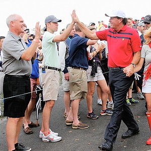Team USA's Phil Mickelson with his wife Amy walk off the 17th hole after the team of Mickelson/Bradley defeated the Els/de Jonge team 2&1 during the Day 3 Four-ball Matches at the Muirfield Village Golf Club.