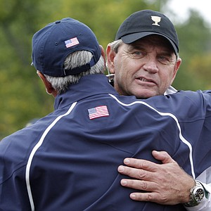 Nick Price (right) gets a hug from opposing captain Fred Couples on the final day of the U.S.' 2013 Presidents Cup win at Muirfield Village.