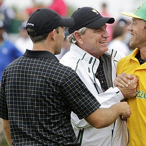 Internationals captain Nick Price, center, and Charl Schwartzel, from left, and Nick Price greet Graham DeLaet after his win on the final day of the U.S.' 2013 Presidents Cup win at Muirfield Village.
