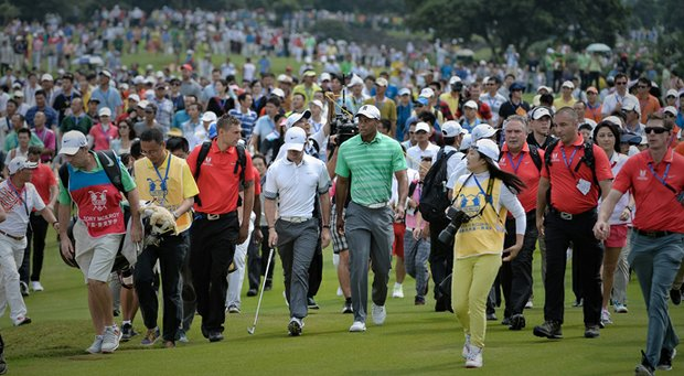 Tiger Woods (center right) and Rory McIlroy (centre left) walk side by side during their exhibition at Mission Hills.