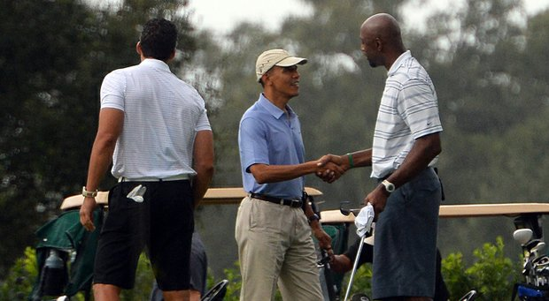 U.S. President Barack Obama (C) shakes hands with former NBA basketball player Alonzo Mourning as he arrives to play golf at Grande Oaks Golf Club in Fort Lauderdale, Florida, on Nov. 9.