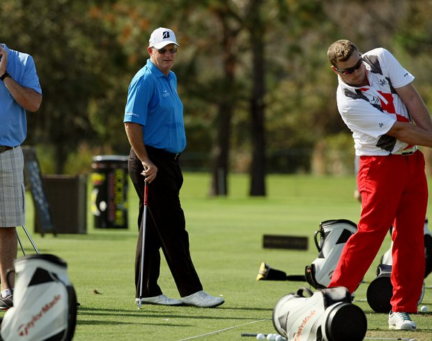 Sandy Lyle, center, watches over his son James Lyle on the range on Wednesday of the PNC Father/Son Challenge at The Ritz Carlton Golf Club of Orlando.