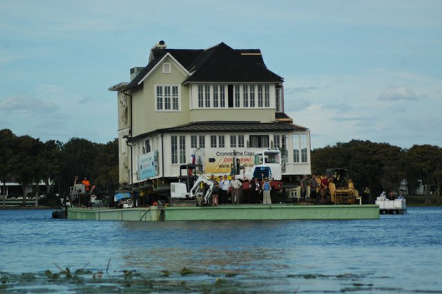 Preservation Capen organizers wave from their house boat as it floats across Lake Osceola Tuesday.