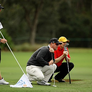 David Duval kneels down next to pro-am partner, Jay Leonard, to read a putt the PNC Father/Son Challenge Pro-Am at The Ritz Carlton Golf Club of Orlando. At left is Nick Karavities, caddie/step-son.