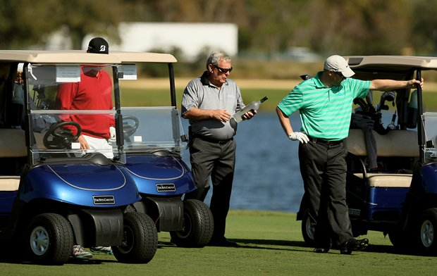 Fuzzy Zoeller looks at a liqueur bottle after autographing it at No. 18 during the PNC Father/Son Challenge Pro-Am at The Ritz Carlton Golf Club of Orlando.