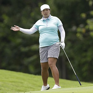 China's Shanshan Feng gestures as she watches her ball land on the ninth green during her final round at the Malaysian LGPA event in Kuala Lumpur, Sunday, Oct. 13, 2013.