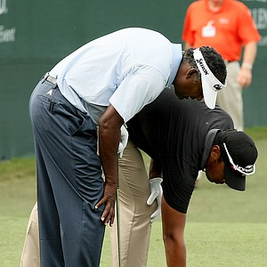 Vijay Singh and his son, Qass, carefully examine where to place the ball at No. 18 on Saturday at the PNC Father/Son Challenge at The Ritz Carlton Golf Club of Orlando.