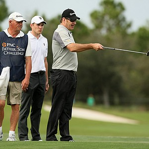 Nick Faldo with his sone, Matthew, center and their caddie read a putt at No. 18 on Saturday at the PNC Father/Son Challenge at The Ritz Carlton Golf Club of Orlando.