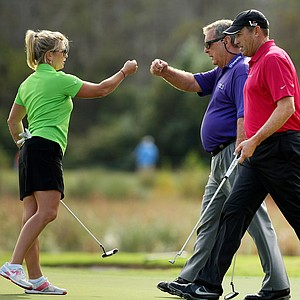 Gretchen Chappo fist bumps with her father, Fuzzy Zoeller, after making her putt on Sunday at the PNC Father/Son Challenge at The Ritz Carlton Golf Club of Orlando. At right is Dave Stockton, Jr.