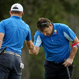 Sir Nick Faldo bows down to accept a congratulatory handshake from is son Matthew on Sunday at the PNC Father/Son Challenge at The Ritz Carlton Golf Club of Orlando.