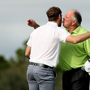 Mark O'Meara plants a kiss on his son, Shaun, after they finish their round on Sunday at the PNC Father/Son Challenge at The Ritz Carlton Golf Club of Orlando.