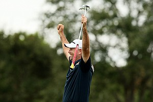 Stewart Cink looks toward his son, Connor, and raises his hands in the air after sinking an eagle putt on Sunday at the PNC Father/Son Challenge at The Ritz Carlton Golf Club of Orlando.