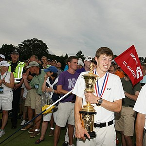 Matt Fitzpatrik holds the Havemeyer Trophy on the side of the 15th green where he won the  2013 U. S. Amateur at The Country Club.