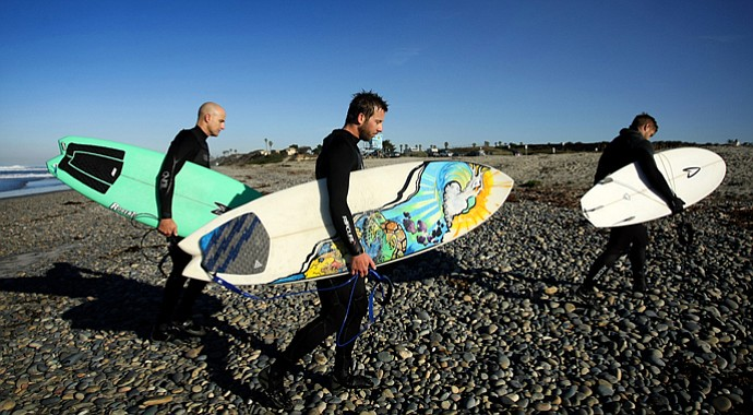 TaylorMade Golf industry guys, from left, Eric Loper, Scott Mayers, and Christopher Piniarski leave the beach after surfing at South Ponto State Beach in the Carlsbad area near San Diego, Calif.