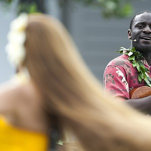 A hula dancer performs as Kamakakehau Fernandez plays a ukulele before the start of the first round of Tournament of Champions.