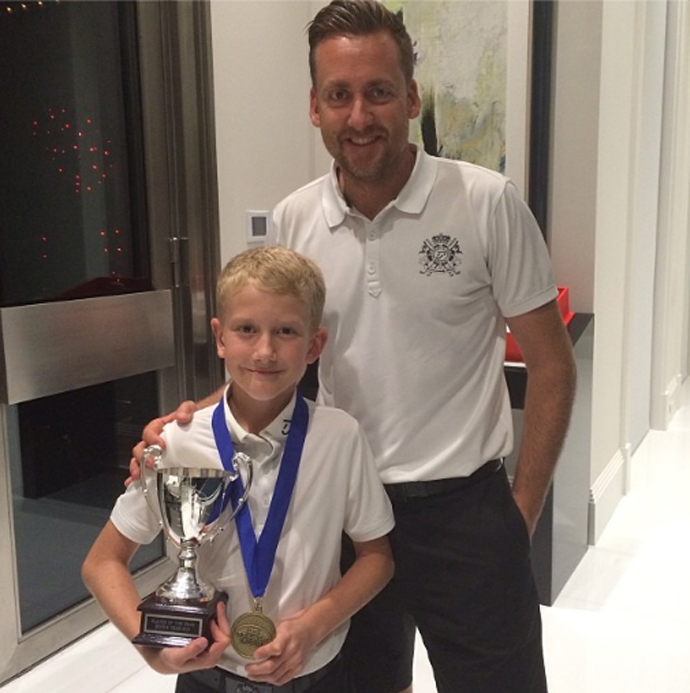 Ian Poulter and his son, Luke James, pose with the trophy after winning the boys 9 division.
