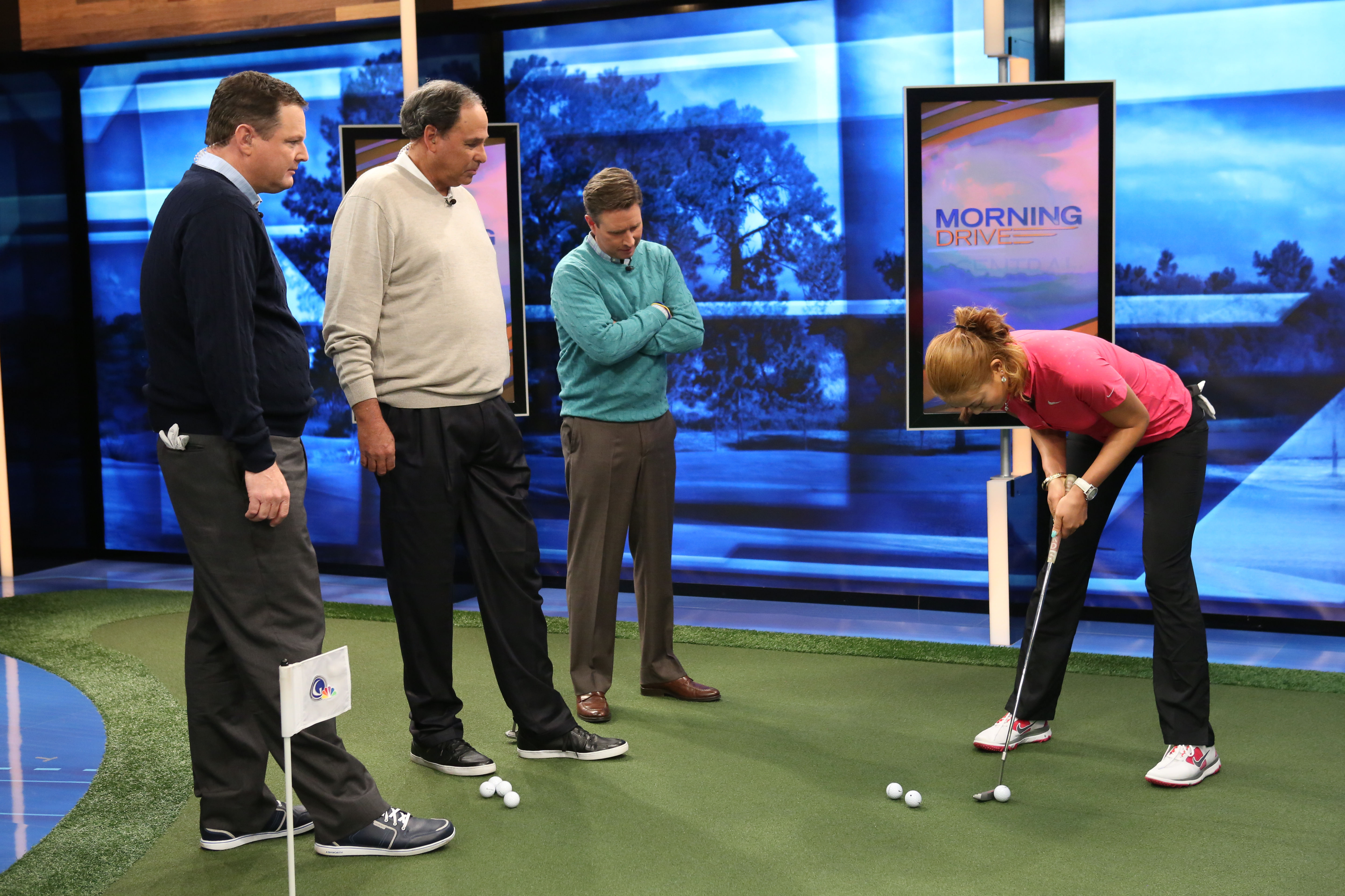 Michelle Wie (right) shows off her putting stroke to Charlie Rymer, Phil Blackmar and Gary Williams during Golf Channel's Morning Drive on Thursday.