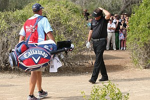 Phil Mickelson looks dejected with his caddie Jim 'Bones' MacKay after he double hit his second shot from under a bush on the 13th hole during the final round of the Abu Dhabi HSBC Golf Championship.