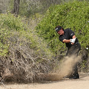 Phil Mickelson plays his fourth shot right-handed from under a bush on the 13th hole during the final round of the Abu Dhabi HSBC Golf Championship.