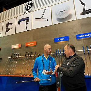Kyle Ulrikson, LPGA rep with Rife shows putters to Joseph Kreder, COO, Dewey Indoor Golf & Sports Grill during the 2014 PGA Merchandise Show at the Orange County Convention Center.